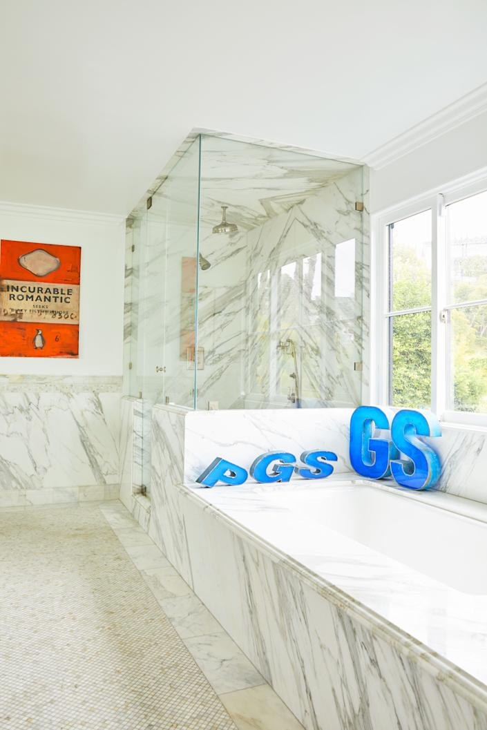 "<div class=""caption""> Steele's marble bathroom (yes, the spouses have separate bathrooms, which they say is ""key to the success of our marriage"") has vintage letters from a former gas station in Beirut and a painting by British writer and artist Harland Miller. </div>"