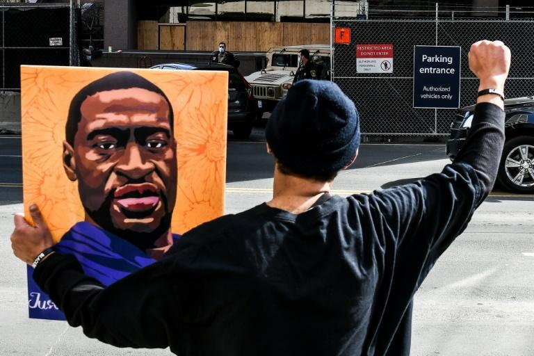 A demonstrator holds a portrait of George Floyd outside the Hennepin County Government Center in Minneapolis, Minnesota