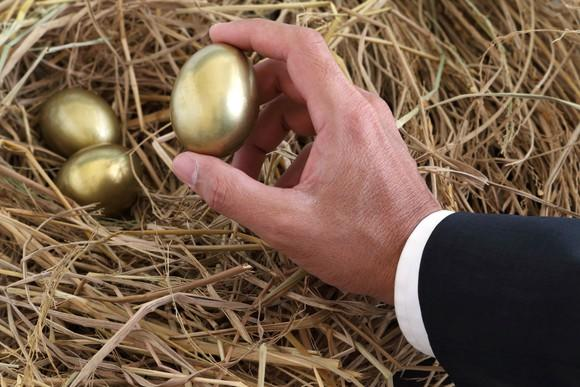 Businessman picking up a golden egg from a nest with several such eggs snuggling inside.