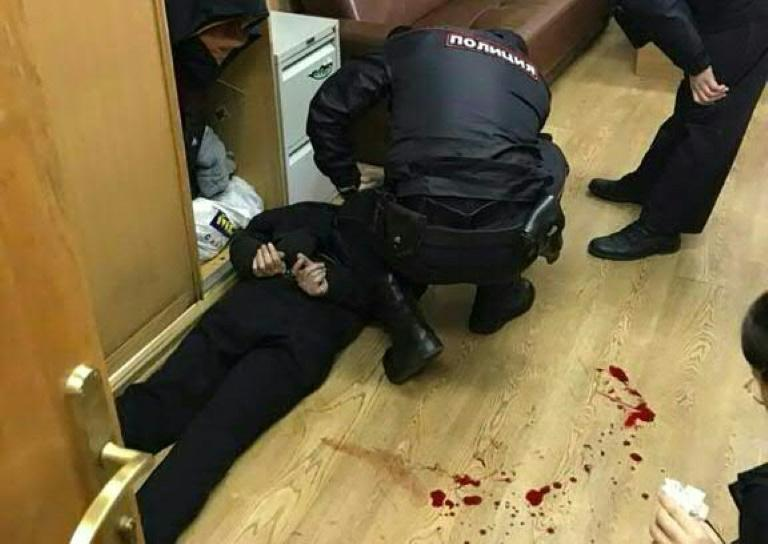 Picture obtained from Vitaly Ruvinsky's Facebook page on October 23, 2017 shows police officers detaining the man (L) who allegedly stabbed Tatiana Felgengauer, a presenter at Echo of Moscow radio station, in Moscow
