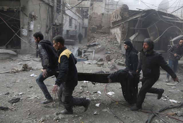 <p>Syrian civil defence volunteers carry away an injured man after reported regime air strikes in the rebel-held town of Jisreen, in the besieged Eastern Ghouta region on the outskirts of the capital Damascus, on Feb. 8, 2018. (Photo: Abdulmonam Eassa/AFP/Getty Images) </p>
