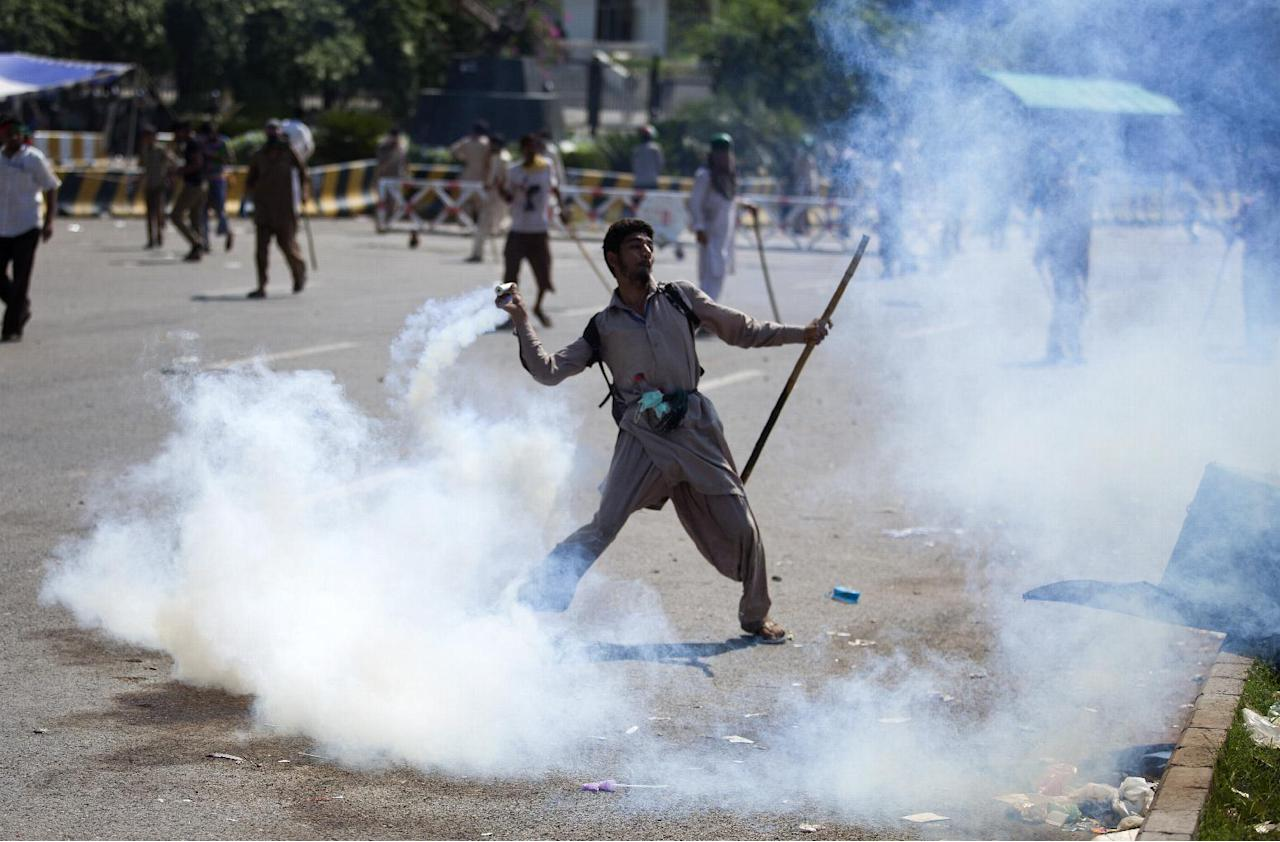 A Pakistani protester throws tear gas shell back towards police during a protest in Islamabad, Pakistan, Sunday, Aug. 31, 2014. Pakistani police clash with scattered pockets of anti-government protesters trying to advance on the prime minister's residence after a night of violence that saw hundreds wounded and the first death Sunday in more than two weeks of demonstrations. (AP Photo/B.K. Bangash)