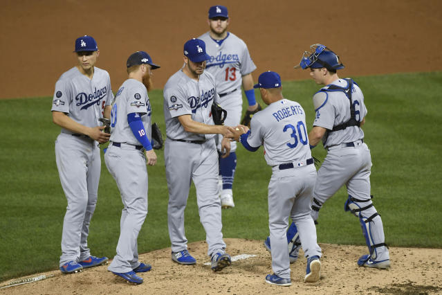 Los Angeles Dodgers manager Dave Roberts (30) takes the ball from starter Rich Hill (44) during a pitching change in the third inning in Game 4 of a baseball National League Division Series against the Washington Nationals, Monday, Oct. 7, 2019, in Washington. (AP Photo/Susan Walsh)
