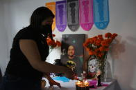 Pediatrician Kenya Navidad, 33, lights candles on a Day of the Dead altar for her husband Daniel Silva Montenegro, a doctor who died from symptoms related to COVID-19, at their home in Mexico City, Saturday, Oct. 31, 2020. The weekend holiday isn't the same in a year so marked by death in a country where more than 90,000 people have died of COVID-19, many cremated rather than buried and with cemeteries forced to close. (AP Photo/Ginnette Riquelme)