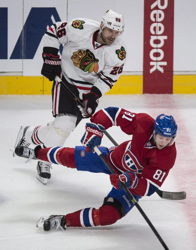 Montreal Canadiens' Lars Eller is tripped by Chicago Blackhawks' Michal Handzus during the second period of an NHL hockey game Saturday, Jan. 11, 2014, in Montreal. (AP Photo/The Canadian Press, Paul Chiasson)