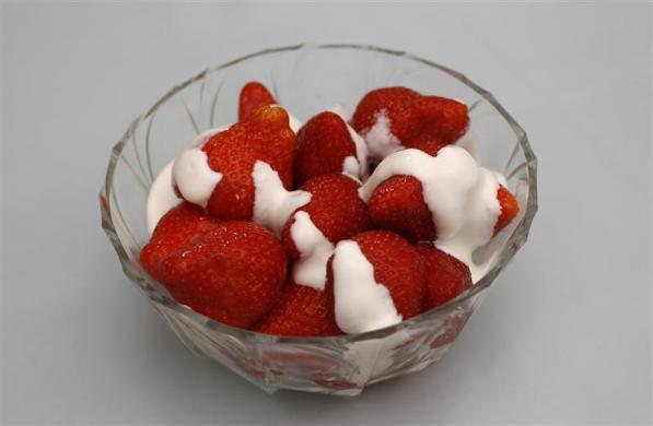 A traditional British desert of a bowl of strawberries and cream.