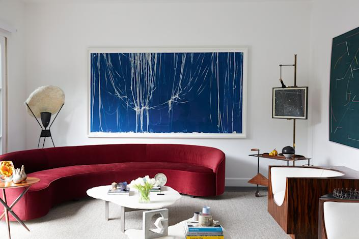 "<div class=""caption""> In the living room, a curvaceous sofa by Brazilian studio Neobox pairs nicely with Jorge Zalszupin's Cube chairs from the 1960s, made in richly veined jacarandá wood. The large blue artwork is a cyanotype by Swiss-American artist Christian Marclay. To the right, we see a 1950s easel by Angelo Lelli holding a Fred Tomaselli photogram, and a Zalszupin tea trolley. </div>"