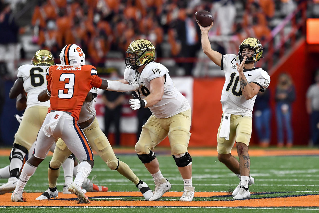 Wake Forest quarterback Sam Hartman, right, throws a pass during the first half of an NCAA college football game against Syracuse in Syracuse, N.Y., Saturday, Oct. 9, 2021. (AP Photo/Adrian Kraus)