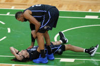 Orlando Magic center Khem Birch (24) checks on Cole Anthony, who had landed on the floor during the second half of the team's NBA basketball game against the Boston Celtics, Friday, Jan. 15, 2021, in Boston. (AP Photo/Elise Amendola)