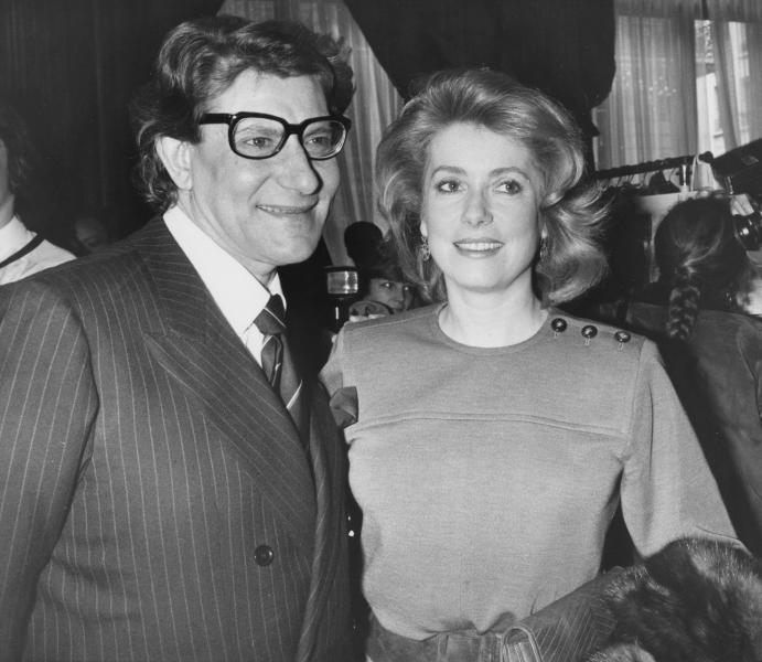 "FILE - In this Jan. 30 1985 file photo, French actress Catherine Deneuve congratulates French fashion designer Yves Saint Laurent after the presentation of spring-summer haute couture collection in Paris. Denueve's family said in a statement released Wednesday Nov. 6, 2019, that the 76-year-old actress suffered a ""very limited and therefore reversible"" stroke. (AP Photo/Alexis Duclos, File)"