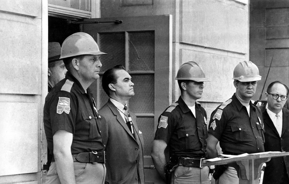 FILE - In this June 11, 1963 file photo, Gov. George Wallace blocks the entrance to the University of Alabama as he turned back a federal officer attempting to enroll two black students at the university campus in Tuscaloosa, Ala. The University of Alabama at Birmingham has removed the name of four-term governor and presidential candidate George C. Wallace from a campus building over his support of racial segregation. A resolution unanimously approved by trustees Friday, Feb. 5, 2021, said Wallace rose to power by defending racial separation and stoking racial animosity. (AP Photo/File)