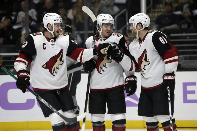 Arizona Coyotes center Phil Kessel, right, celebrates his goal with defenseman Oliver Ekman-Larsson, left, of Sweden, and center Clayton Keller, center, during the first period of an NHL hockey game against the Los Angeles Kings in Los Angeles, Saturday, Nov. 23, 2019. (AP Photo/Alex Gallardo)