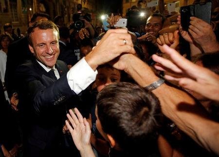 FILE PHOTO: French President Emmanuel Macron greets well-wishers as he arrives in Arles, France, July 19, 2017.  REUTERS/Jean-Paul Pelissier/File Photo