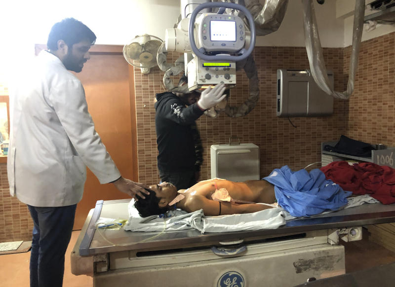 """Doctors treat Mohammad Sameer, 17, for a gunshot wound to his chest that he said he received while standing on his family's apartment terrace watching Hindu mobs enter Mustafabad, at Guru Teg Bahadur Hospital in New Delhi, India, Wednesday, Feb. 26, 2020. """"When Sameer was shot, I took him on my shoulders and ran downstairs,"""" said the boy's father, Mohammad Akram. """"But the when the mob saw us, they beat me and my injured son. He was bleeding very badly. While they were beating with sticks, they kept on chanting Jai Shri Ram slogans and threatened to barge inside our homes."""" The clashes between Hindu mobs and Muslims protesting a contentious new citizenship law that fast-tracks naturalization for foreign-born religious minorities of all major faiths in South Asia except Islam escalated Tuesday. (AP Photo/Sheikh Saaliq)"""
