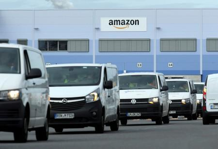 FILE PHOTO: Delivery vehicles leave an Amazon logistics centre in Mannheim