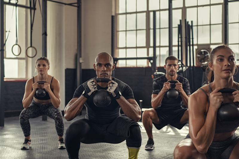 Fitness women and determined men exercising with kettlebell at cross training gym. Group of young people doing a kettle bell exercise along with squatting. Multiethnic group of fit class doing crouch exercise while holding weight.
