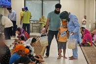 """Raghuvinder Singh, right, greets a child while helping to serve food after a Sikh worship service at a gurdwara in Glen Rock, N.J., Sunday, Aug. 15, 2021. Baba Punjab Singh, a Sikh priest visiting from India, was shot in the head by a white supremacist Army veteran in Wisconsin in 2012, and left partially paralyzed. He died from his wounds in 2020. Over seven years, the priest's son, Raghuvinder Singh, split his time between caring for his father in Oak Creek and working in Glen Rock, New Jersey, as assistant priest at a gurdwara there. Raghuvinder said the greatest lesson his father taught him was how to embody """"chardi kala,"""" which calls for steadfast optimism in the face of oppression. (AP Photo/Seth Wenig)"""