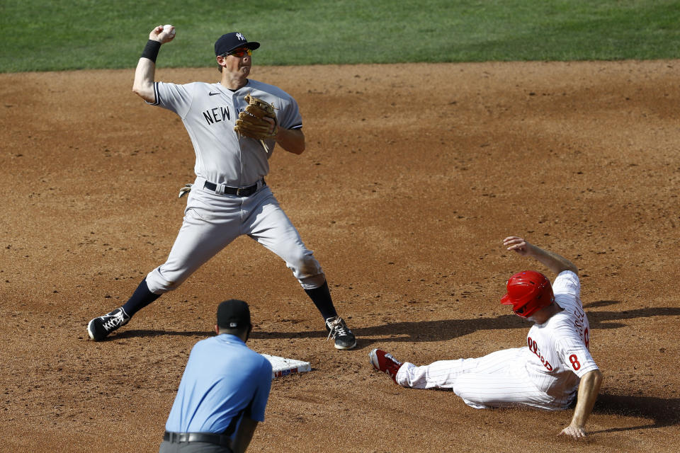 New York Yankees second baseman DJ LeMahieu, left, throws to first after forcing out Philadelphia Phillies' Phil Gosselin, right, at second on a run scoring fielder's choice hit by Roman Quinn during the third inning of the first baseball game in doubleheader, Wednesday, Aug. 5, 2020, in Philadelphia. (AP Photo/Matt Slocum)
