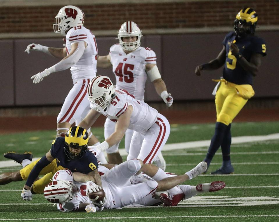 Michigan Wolverines' Ronnie Bell, left, makes the tackle on Wisconsin's Scott Nelson, after an interception on Joe Milton (5) in the first quarter at Michigan Stadium in Ann Arbor, Saturday, Nov. 14, 2020.