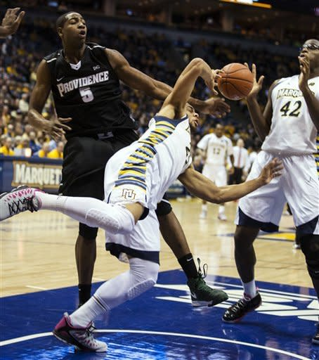 Marquette's Jake Thomas, center, is fouled by Providence's Sidiki Johnson (5) as he attempts to shoot during the first half of an NCAA college basketball game, Saturday, Jan. 26, 2013, in Milwaukee. (AP Photo/Tom Lynn)