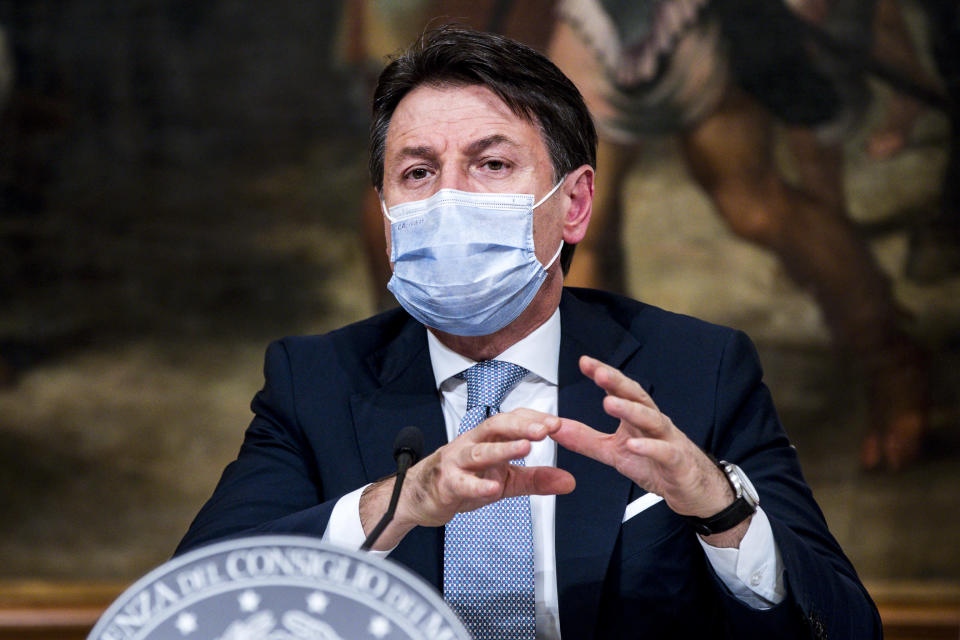 """Italian Premier Giuseppe Conte announces new restrictions to curb the spread of coronavirus, in Rome, Wednesday, Nov. 4, 2020. Four regions in Italy are being put under severe lockdown, forbidding people to leave their homes except for essential reasons such as food shopping and work in a bid to slow surging COVID-19 infections and prevent hospitals from being overwhelmed. Premier Giuseppe Conte on Wednesday night announced what he described as """"very stringent"""" restrictions on the so-called """"red zone"""" regions of high risk: Lombardy, Piedmont, Valle d'Aosta in the north and Calabria, the region forming the """"toe"""" in the south of the Italian peninsula. (Angelo Carconi/Pool Photo via AP)"""
