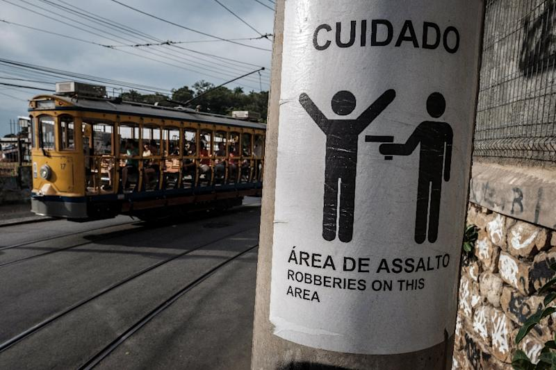 Rio's famous street car passes by a sign warning against robberies on an electricity pole in Santa Teresa, home to favelas where firefights between rival gangs and police are a common sight