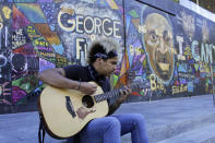"""Shane Braswell, who has participated in Black Lives Matter protests this summer, plays guitar in front of a mural covering the entrance to an Apple store, Aug. 27, 2020 in Portland, Ore. Braswell said President Donald Trump's portrayal of Portland as a violent city overcome by mobs of protesters is inaccurate and grossly exaggerated. """"I hate when people say, 'Portland riots' or 'Seattle riots.' You see it as a riot because it is something that's going against your administration or your beliefs or your principles when the majority of the country is fed up and marching arm-in-arm,"""" he said. (AP Photo/Gillian Flaccus)"""
