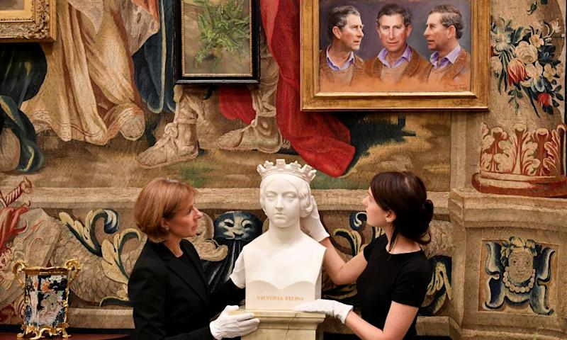 A painting of Prince Charles looks down on curators preparing a marble bust of Queen Victoria for the exhibition.