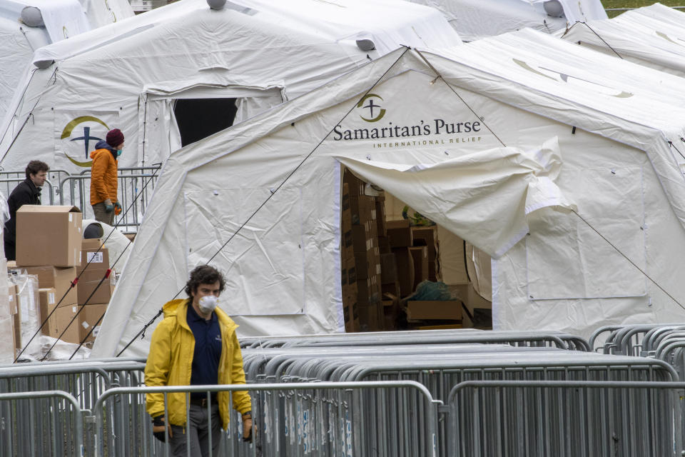 A Samaritan's Purse crew and medical personnel work on preparing to open a 68 bed emergency field hospital specially equipped with a respiratory unit in New York's Central Park, Tuesday, March 31, 2020, in New York. The new coronavirus causes mild or moderate symptoms for most people, but for some, especially older adults and people with existing health problems, it can cause more severe illness or death. (AP Photo/Mary Altaffer)