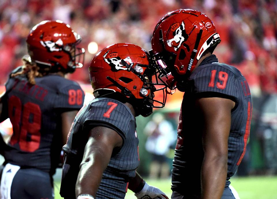 Wolfpack running back Zonovan Knight (7) celebrates with wide receiver C.J. Riley III (19) after scoring against the Bulls.