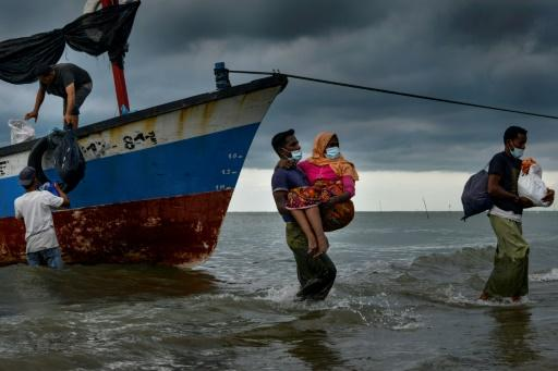 Acehnesse fishermen help carry a Rohingya child ashore after locals defied authorities who didn't want the asylum seekers to land