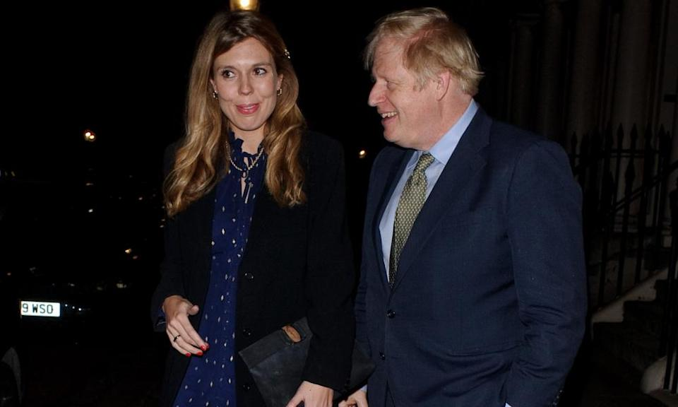 Boris Johnson (R) and Carrie Symonds seen attending Evgeny Lebedev's Christmas Party on December 13, 2019 in London, England.