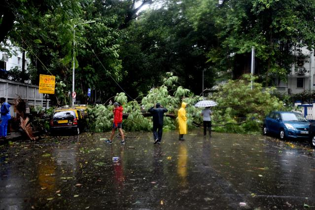 MUMBAI, INDIA - JUNE 03: Indian workers clear a tree that fell on a road due to strong winds triggered by Cyclone Nisarga in Mumbai, India on June 03, 2020. A storm in the Arabian Sea off India's west coast intensified into a severe cyclone on Wednesday, gathering speed as it barreled toward India's financial capital of Mumbai. Nisarga was forecast to drop heavy rains and winds gusting up to 120 kilometers (75 miles) per hour when it makes landfall Wednesday afternoon as a category 4 cyclone near the coastal city of Alibagh, about 98 kilometers (60 miles) south of Mumbai, India's Meteorological Department said. (Photo by Imtiyaz Shaikh/Anadolu Agency via Getty Images)