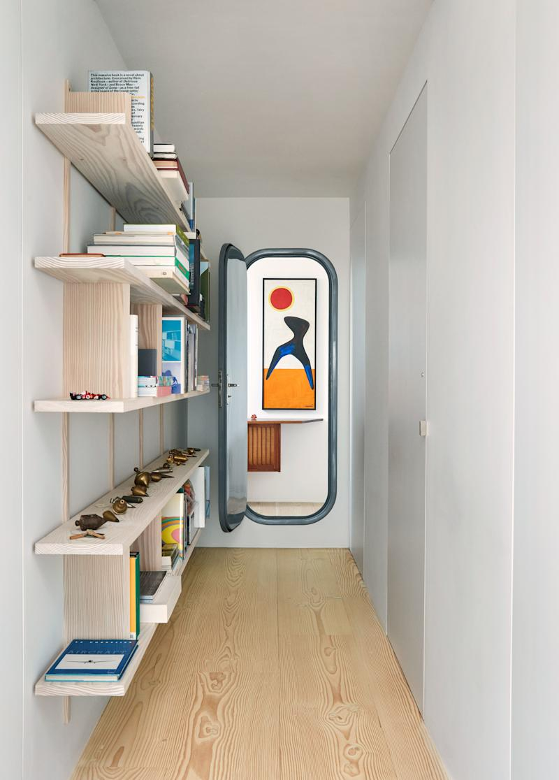 A vintage Charlotte Perriand door leads to a tiny chamber, within which an Alexander Calder painting hangs above a wall-hung George Nakashima cabinet.