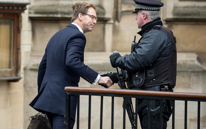 Tobias Ellwood, who gave first aid to fatally wounded Keith Palmer, shakes hands with an armed police officer outside Parliament on Friday morning - Credit: CHRIS J RATCLIFFE/AFP