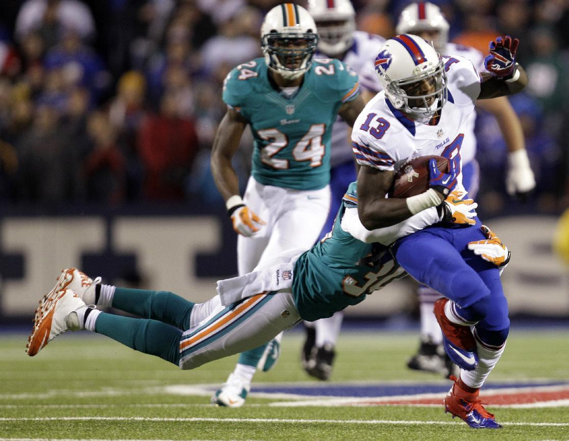 Buffalo Bills wide receiver Stevie Johnson (13) is tackled by Miami Dolphins strong safety Chris Clemons (30) during the first half of an NFL football game on Thursday, Nov. 15, 2012, in Orchard Park, N.Y. (AP Photo/Gary Wiepert)