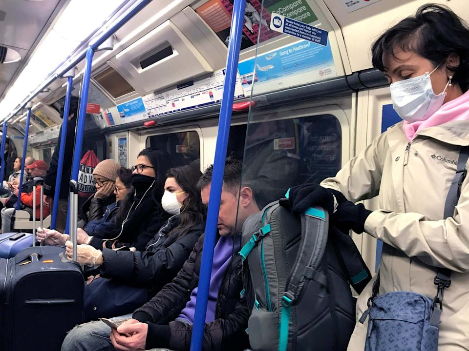 People wear masks and gloves as they travel on a tube in London, Friday, March 13, 2020: AP