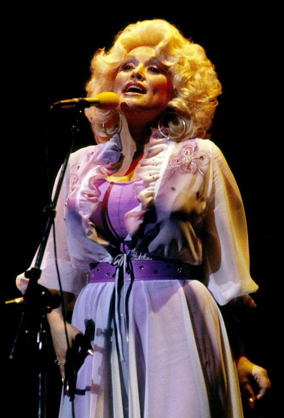 <p>Early on in Dolly's career, the singer stuck mostly to pastels—unlike the vibrant colors we're used to seeing on her today. This breezy ensemble feels reminiscent of a simpler life back home in Tennessee, elevated with a bright purple belt and delicate beading.</p>