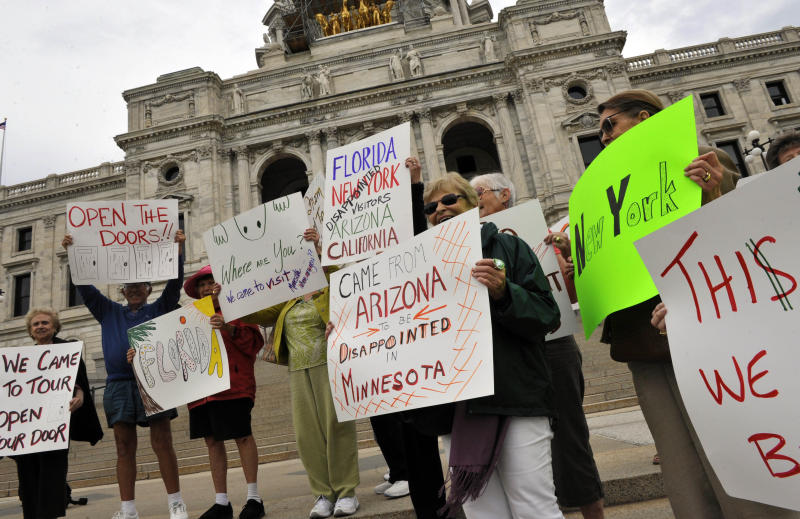 A group of touring senior citizens from around the country on a tour out of Florida expressed their disappointment on the steps of the closed Minnesota State Capitol Tuesday, July 12, 2011 in St. Paul,  Minn. The group had hoped to visit the Capitol, History Center and other sites which have been closed due to the government shutdown which began July 1. (AP Photo/Jim Mone)