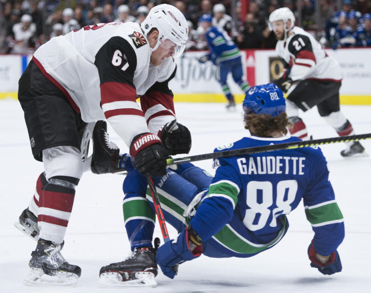 Arizona Coyotes left wing Lawson Crouse (67) puts Vancouver Canucks centre Adam Gaudette (88) to the ice during the third period of an NHL hockey game Thursday, Jan. 16, 2020, in Vancouver, British Columbia. (Jonathan Hayward/The Canadian Press via AP)