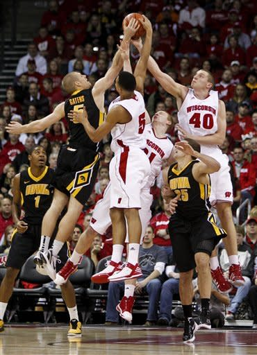 Iowa's Matt Gatens, left, and Eric May (25) battle for a rebound against Wisconsin's Ryan Evans (5), Mike Bruesewitz and Jared Berrgren (40) during the first half of an NCAA college basketball game Saturday, Dec. 31, 2011, in Madison, Wis. (AP Photo/Andy Manis)
