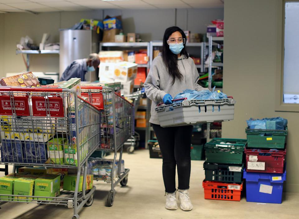 A volunteer wearing protective personal equipment (PPE) organises food parcels at the Sufra NW London food bank in Neasden, which provides emergency supplies of essential food to individuals and families struggling during the lockdown. Picture date: Friday May 15, 2020