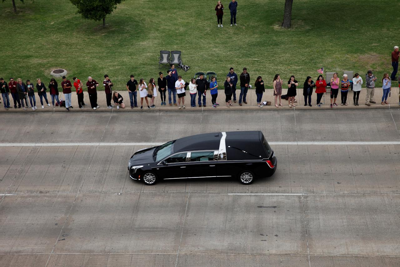 The hearse carrying former first lady, Barbara Bush, drives past onlookers on George Bush Drive, followed by her husband, former U.S. President George H.W. Bush, son, former U.S. President George W. Bush, and their family, to the George Bush Presidential Library and Museum for her burial in College Station, Texas, U.S., April 21, 2018.    REUTERS/Spencer Selvidge