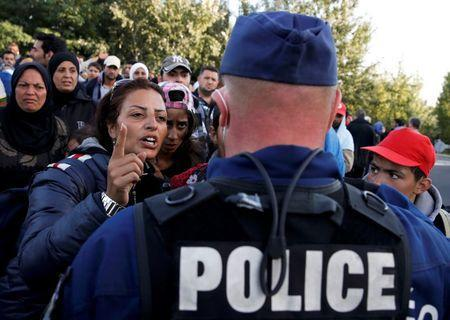 Migrants address a Hungarian police officer at collection point in the village of Roszke, Hungary, September 7, 2015. REUTERS/Marko Djurica