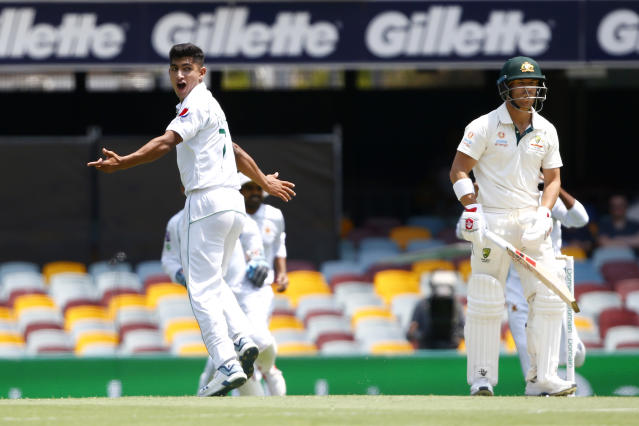Pakistan's Naseem Shah, left, celebrates the wicket of Australia's David Warner, right, before the decision was overturned due to a no ball called during their cricket test match in Brisbane, Australia, Friday, Nov. 22, 2019. (AP Photo/Tertius Pickard)
