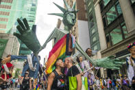 Christopher Williams and his husband Ed Stallsworth kiss while marching with the Pride Puppets at the Queer Liberation March on Sunday, June 27, 2021, in New York. (AP Photo/Brittainy Newman)