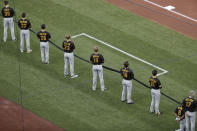 Members of the Pittsburgh Pirates hold a black ribbon in honor of Black Lives Matter before the start of a baseball game against the St. Louis Cardinals on opening day for the two teams Friday, July 24, 2020, in St. Louis. (AP Photo/Jeff Roberson)