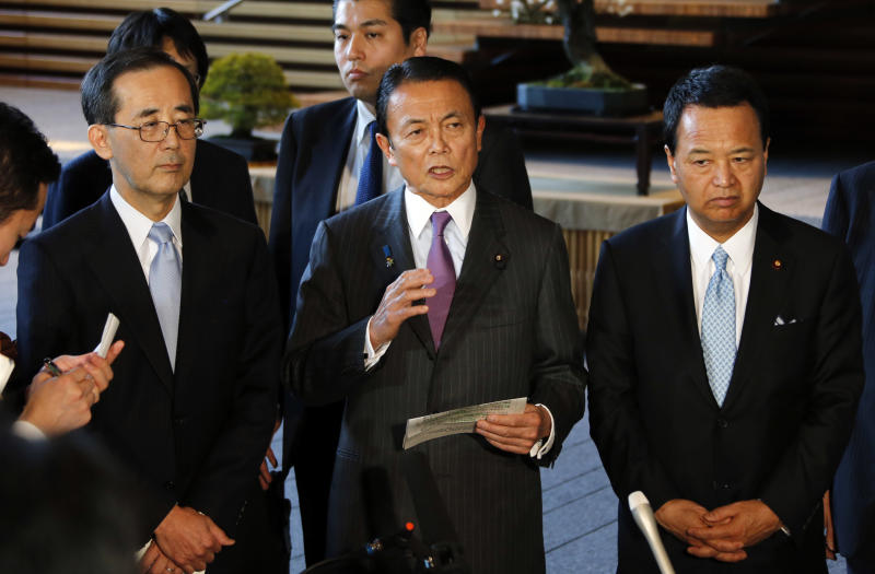 "Japan's Finance Minister Taro Aso, center, along with Economics Minister Akira Amari, right, and Bank of Japan Gov. Masaaki Shirakawa, left, speaks to the reporters after meeting with Prime Minister Shinzo Abe, not in photo, at the prime minister's official residence in Tokyo, Tuesday, Jan. 22, 2013. Japan's Prime Minister Abe declared a ""monetary regime change"" Tuesday as the central bank bowed to government pressure, setting a 2 percent inflation target aimed at helping the country emerge from its prolonged bout of deflation. (AP Photo/Koji Sasahara)"