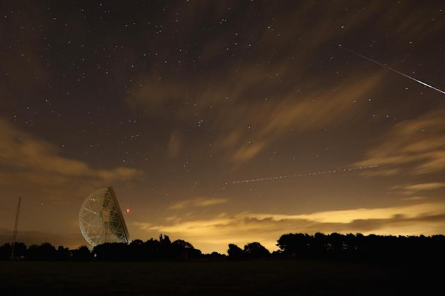 HOLMES CHAPEL, UNITED KINGDOM - AUGUST 13: A Perseid meteor (R) streaks across the sky past the light trail of an aircraft over the Lovell Radio Telescope at Jodrell Bank on August 13, 2013 in Holmes Chapel, United Kingdom.The annual display, known as the Perseid shower because the meteors appear to radiate from the constellation Perseus in the northeastern sky, is a result of Earth's orbit passing through debris from the comet Swift-Tuttle. (Photo by Christopher Furlong/Getty Images)