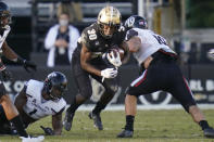 Central Florida running back Greg McCrae (30) runs for yardages against Cincinnati safety James Wiggins, left, and defensive tackle Ethan Tucky, right, during the first half of an NCAA college football game, Saturday, Nov. 21, 2020, in Orlando, Fla. (AP Photo/John Raoux)